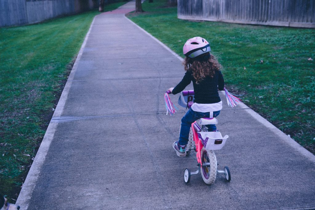 girl on bike with training wheels